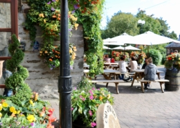 The Old Mill Inn in Pitlochry in the summer sunshine with people enjoying food and drinks at the outdoor tables